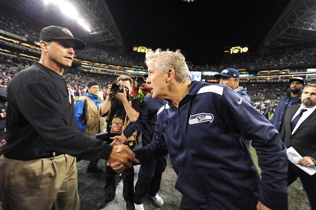 Jim Harbaugh (izquierda) y Pete Carroll. El saludo entre los entrenadores es obligatorio en la NFL, por lo que esta imagen no indica cariño o respeto entre ambos. (Foto Sports Illustrated)