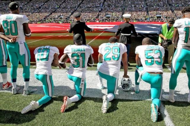 Los jugadores de los Dolphins, Kenny Stills, Michael Thomas, Arian Foster y Jelani Jenkins se arrollidan a modo de protesta.